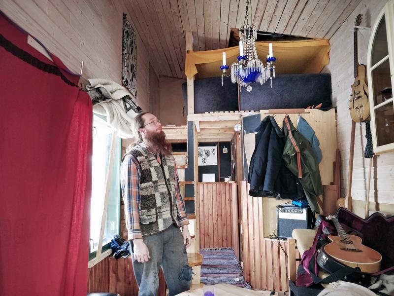 Kristallivalaisin kynttilöillä on ahkerassa käytössä pimeään aikaan oleskelutilassa. Mika Timgrenin takana oikealla ylhäällä makuuparvi, jonka alle rakentuu sauna.