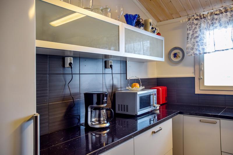 Keittiön tasot ja kaapit ovat alkuperäiset. Kippiovellinen yläkaappi palveli aiemmin myyntitiskin luona.