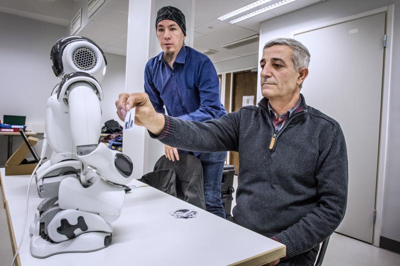 -Pelata, sanoo Mohammad Alou selkeästi ja robotti hyväksyy vastauksen. Kädessään hänellä on lappu, joka kuvastaa kyseisen verbin toimintaa. Taustalla robotiikka-asiantuntija Niko Kaukonen Keski-Pohjanmaan ammattiopistosta.