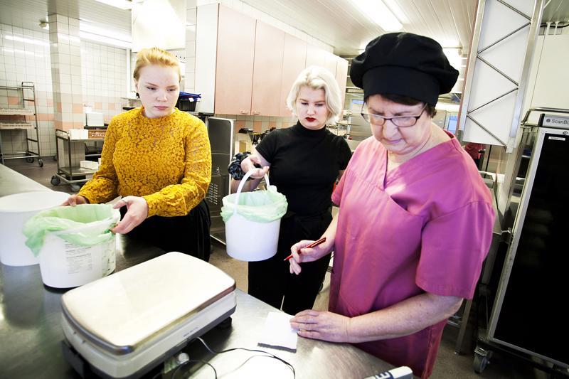 Seida Karukka ja Pinja Kärkkäinen punnitsevat maanantain ruokahävikkiä ruokapalveluvastaava Raija Sorvarin kanssa.