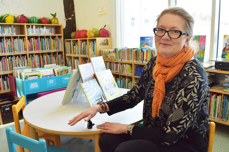Kirjastonjohtaja Sari Seitajärvellä on leimasin valmiina ensi viikolla alkavaa Lukemalla uimaan -kampanjaa varten.