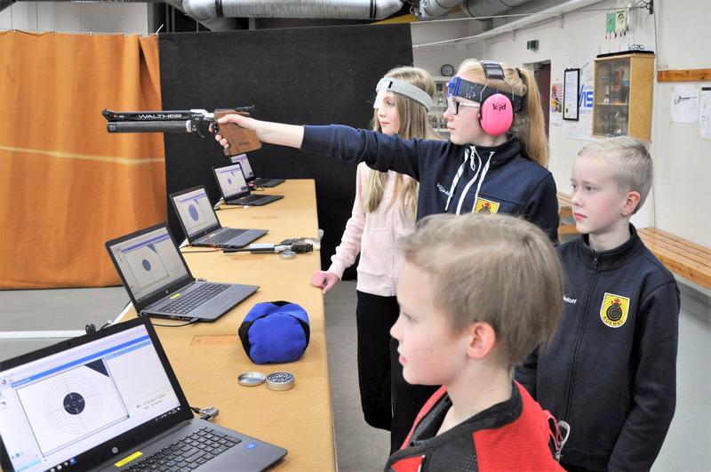 Jeremias Knuuti (vas.), Otso-Aadolf Ahokangas ja Sandra Hagström seuraavat Vilja-Alina Ahokankaan tähtäämistä jäähallin sisäampumaradalla.