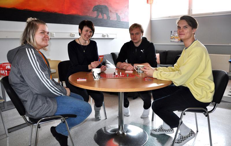 Aino Ruuska, Heli Liuska sekä Jarkko Laakso (oik.) ja Leevi Tikka pelaamassa lautapeliä, joka hankittiin energian käytöstä säästyneillä varoilla.