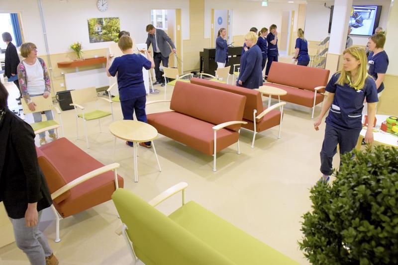 Henkilökunta järjesteli odotussalin kalusteita hyvinvointikeskuksen valoisissa ja lämminsävyisissä tiloissa.
