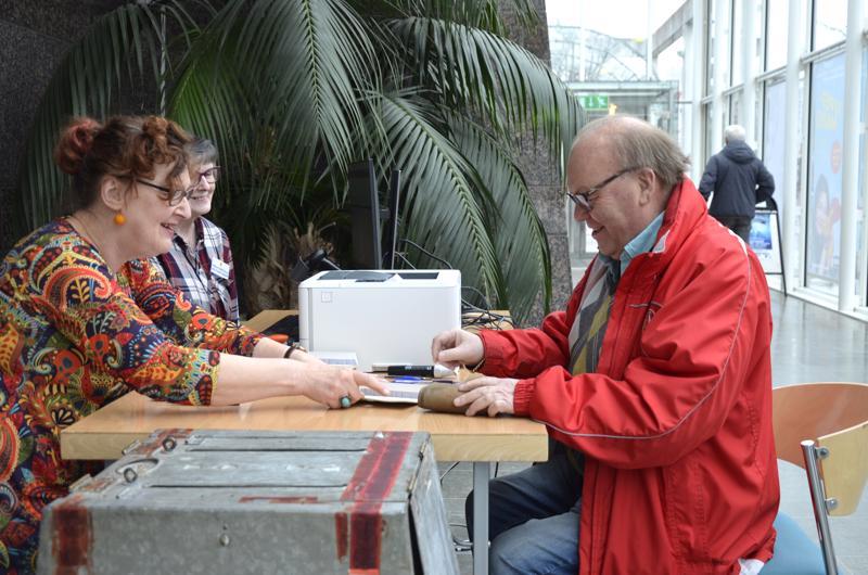 Vaalivirkailijat Eivor Wärn-Auvinen ja Christina Koivusalo huolehtivat, että kaikki sujui mallikkaasti kaupunginkirjaston ennakkoäänestyspaikalla. Äänestysvuorossa Reijo Varila.