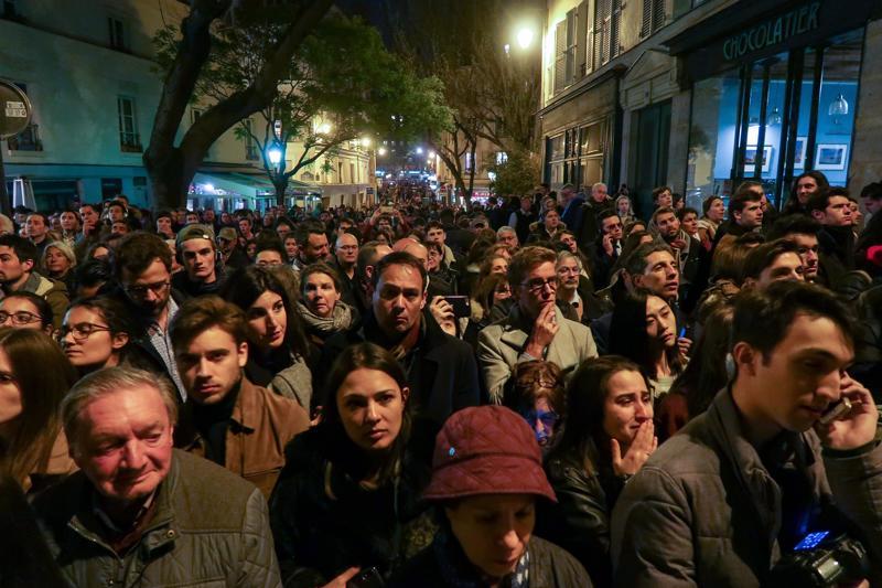 Ihmiset seurasivat järkyttyneinä Notre Damen tulipaloa Pariisin kaduilla maanantai-iltana. Järkytys on tuntunut Suomessa saakka.