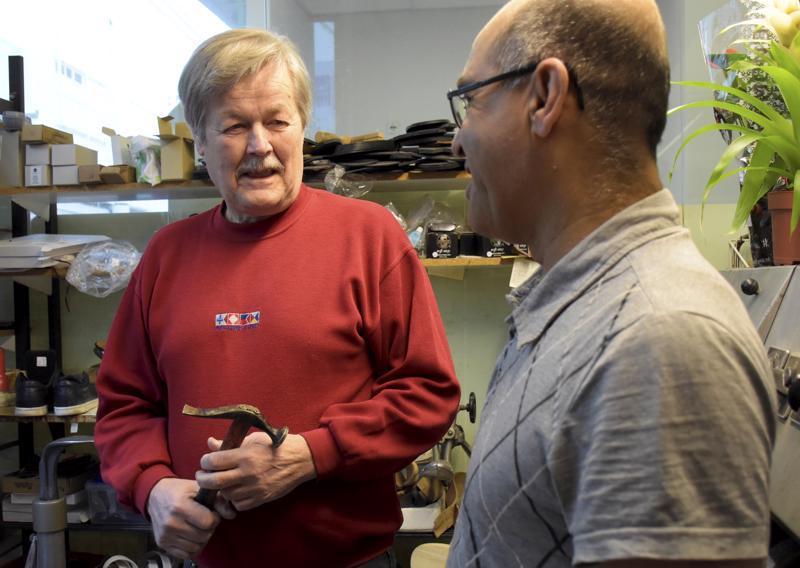 Rolf Ström on luovuttamassa suutarin tärkeimmän työkalun, vasaran, uudelle yrittäjälle Sediqi Mir Aghalle.