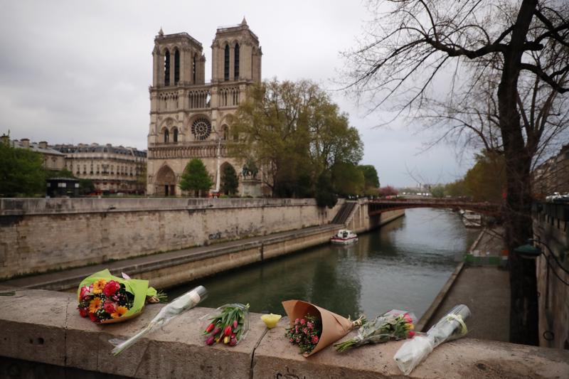 Turistit jättivät kukkia sillalle lähellä Notre Damen palossa turmeltunutta katedraalia tiistaina.