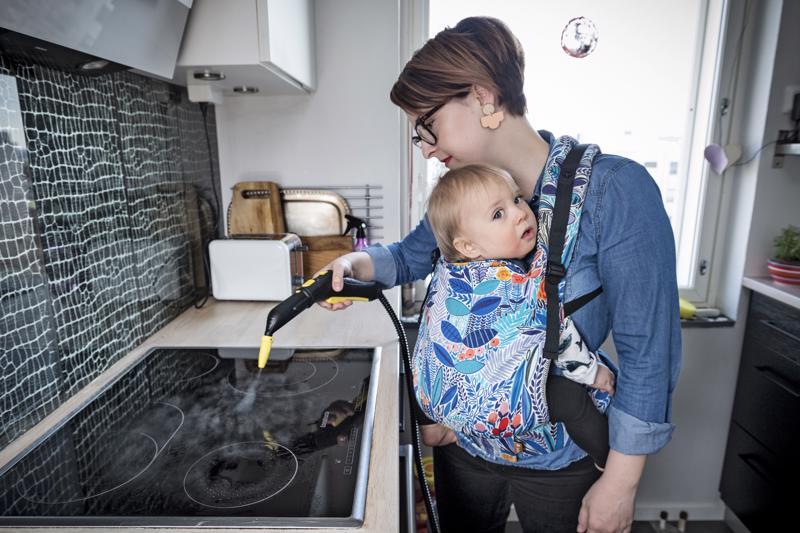 Turkulainen Marjut Ollila siivoaa höyrykoneella keittiönsä välitilan pieni Filip-vauva sylissään. Hän käyttää höyryä kotinsa puhdistamiseen nykyisin viikoittain.