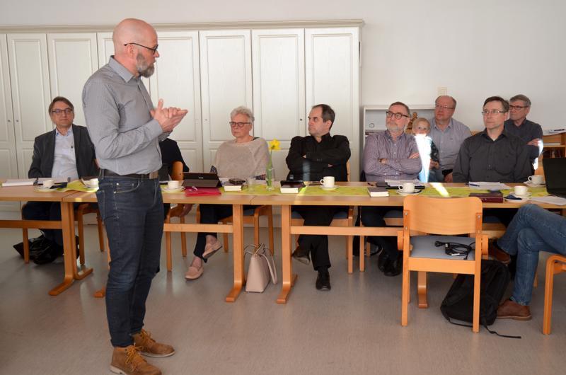 Projektipäällikkö Eero Moilanen selitti kustannusarvion nousuun johtaneita syitä. Pöydän ääressä valtuutetut Mauno Autio, Raili Peltokorpi, Aarne Härö, Leo Mehtälä ja Olli Hiitola kuuntelevat tarkkaavaisesti.