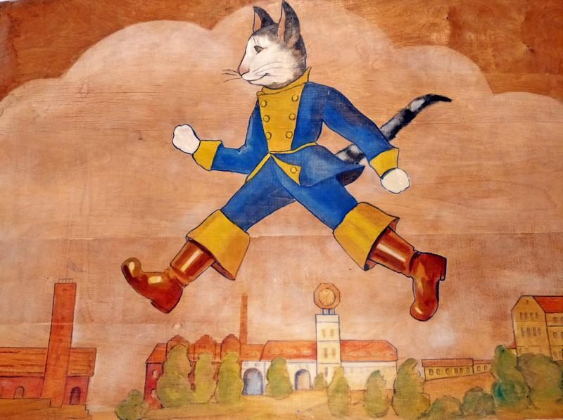 Saapasjalkakissa lentämässä Pietarsaaren ylitse nopein askelin. Vanerille akvarellillä tehdyn teoksen valmistumisvuosi on tuntematon.