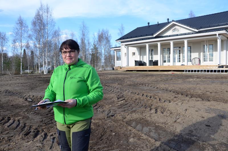 Anu Ainasoja pohtii, miten Halsuan Ylikylässä sijaitsevan talon pihalla voisi parhaiten hyödyntää olemassa olevia materiaaleja kuten kiviä ja ympäristön kasvillisuutta.