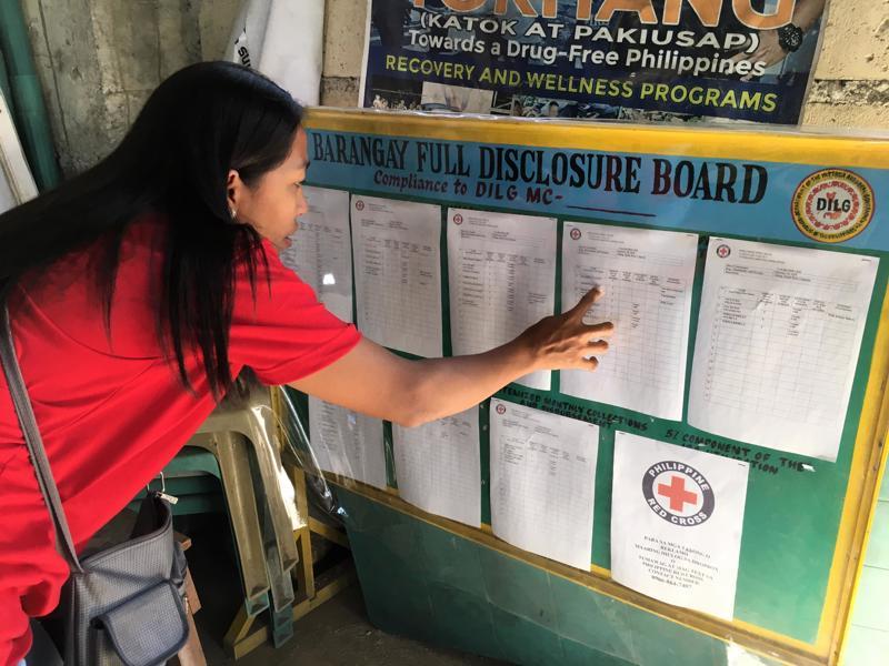Yhteisö itse on päättänyt, ketkä tarvitsevat eniten apua. Cian Carla Ritarita Filippiinien Punaisesta Rististä tutkii avunsaajien nimiä Tambanissa.