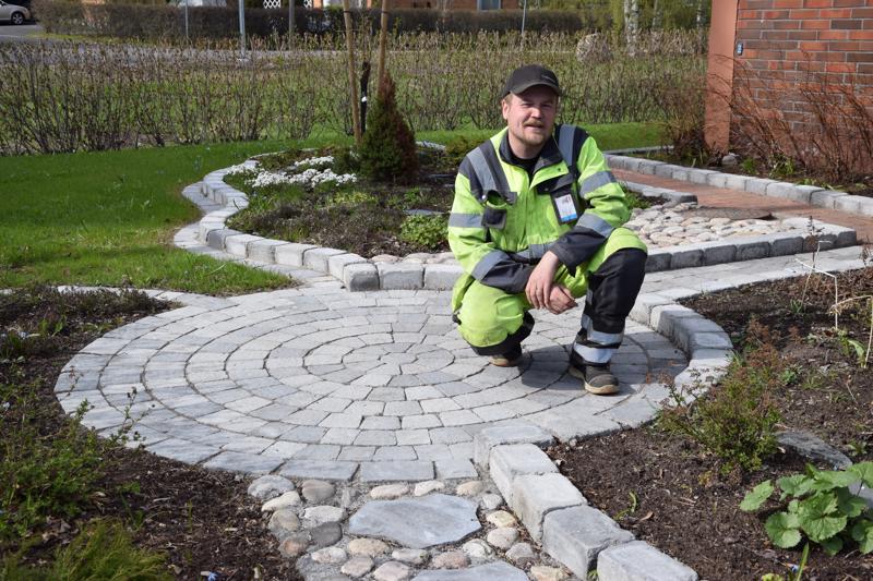 Johannes Nikula tarkistaa asiakaskäynnillä, miltä Maija ja Hans Kauppilan etupihaan rakennettu kiveys ja istutukset näyttävät talven jäljiltä.