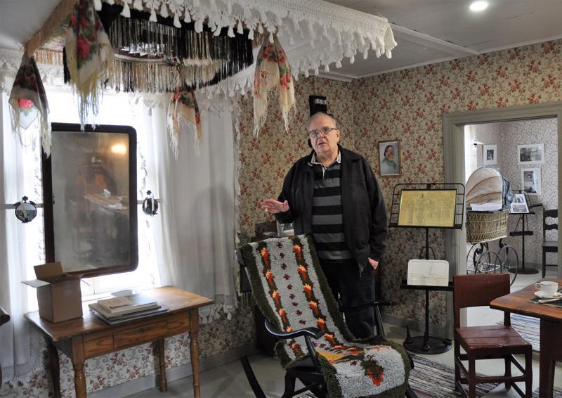 Pekka Kivelä esittelee tuvan keinutuolissa olevaa Ilmari Wirkkalan suunnittelemaa ryijymattoa. Aikanaan Hilja Luoma kutoi keinutuolimaton ja sai sillä palkintoja pohjois-maisissakin käsityökilpailuissa. Kraatarin talon ryijyn on kutonut halsualainen Alli Karhukorpi. Pöydän kulmalla on Tapio Wirkkalan suunnittelema kahvikuppi.