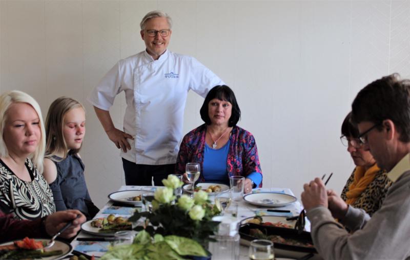 Pöydän päädyssä seisova huippukokki Jyrki Sukula sai ruokailijoilta kehuja tekemistään kalaruoista, vierellään onnekas kilpailun voittaja, pedersöreläinen Marina Lill.