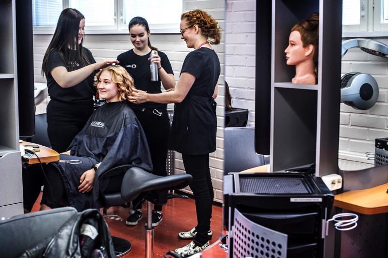 Hius- ja kauneudenhoitoalan opiskelijat Sara Naukkarinen ja Sini Tuominiemi laittavat Jenna Orellin hiuksia Koulutuskeskus Jedussa Nivalassa.