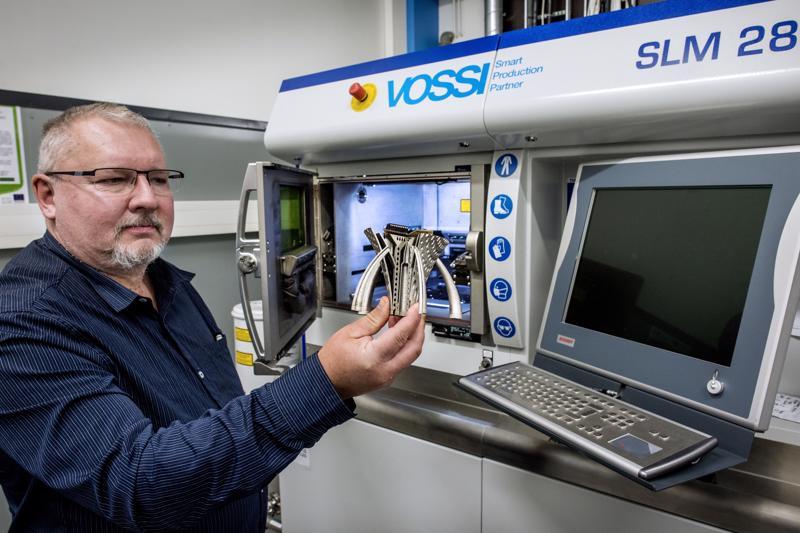 Kehittämispäällikkö Jari Tirkkonen ja alumiinijauheesta tulostettu demo-osa. Tulostaminen nopeuttaa tuotantoa, kun työvaiheet vähenevät.