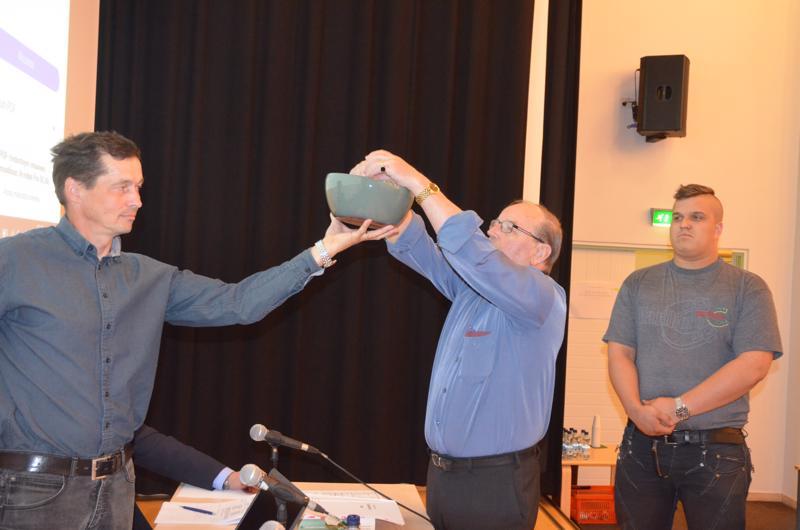 Ratkaisu arvalla. Kunnanvaltuuston puheenjohtaja pitää kulhoa, jossa ovat ehdolla olleiden nimet ja Hannu Kivelä nostaa lapun, jossa lukee Toholammin kunnanhallituksen puheenjohtajan nimi. Takana varmistaa Oskari Laakeri.