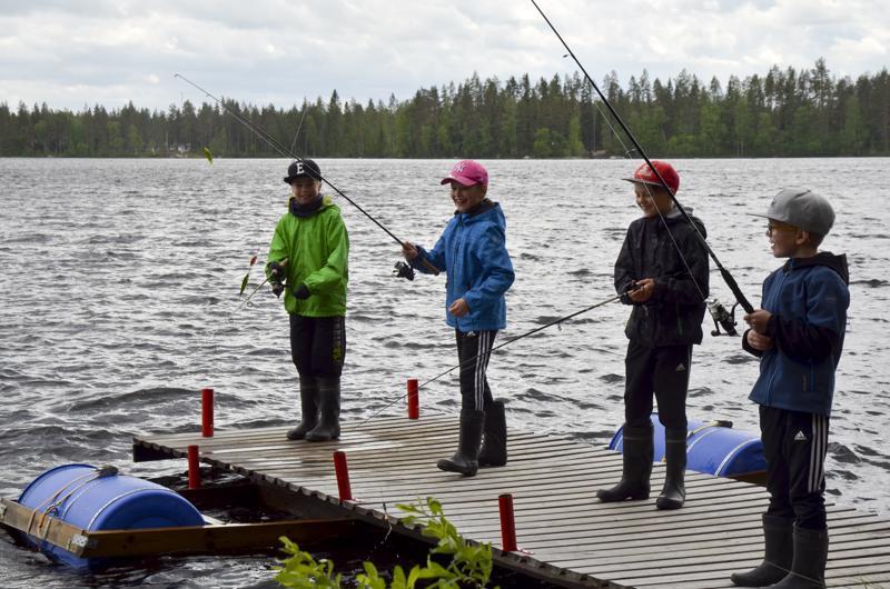Kalastusleiriläiset koittavat kalaonneaan laiturilta.