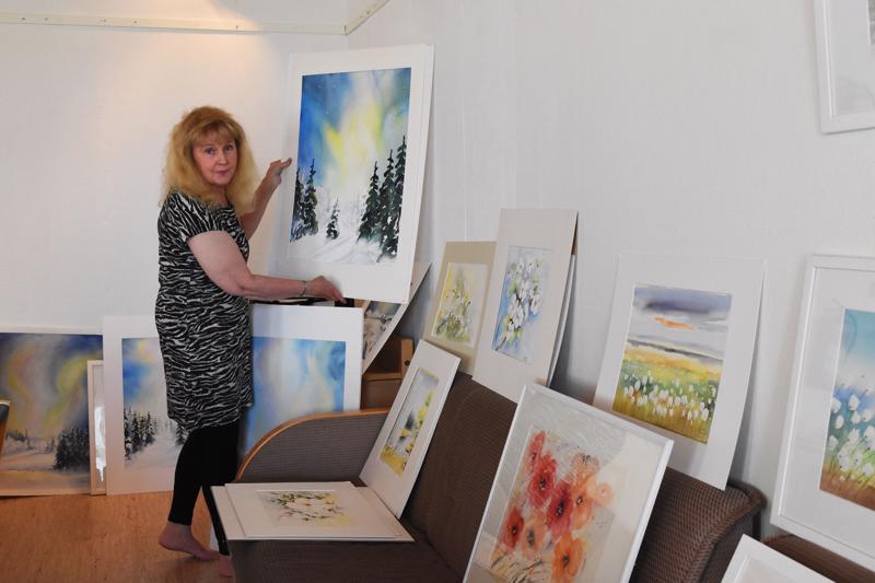Maikki Parkkila pitää akvarellitöistä myös niihin tulevien sattumien takia. Kädessään hänellä on yksi Suomi 100 -aiheisista teoksista.