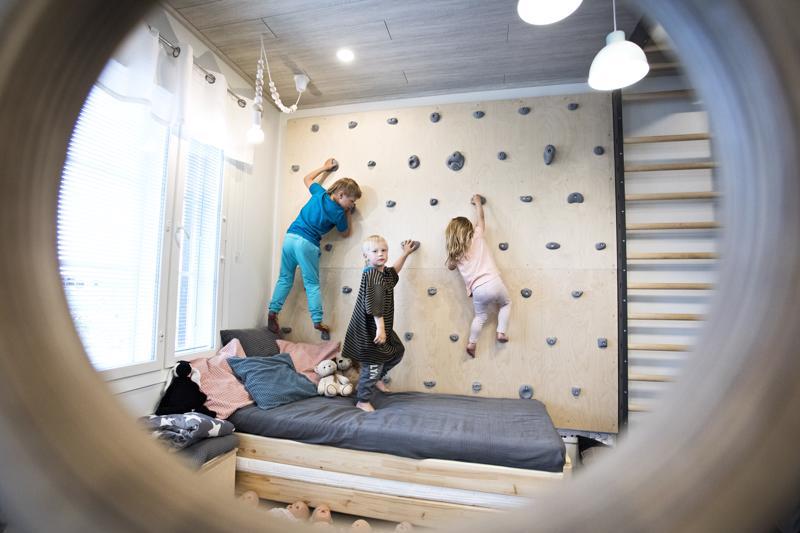 Aatos, Aamos ja Inari kiipeävät kiipeilyseinää pitkin. Äiti Janika Isopahkala suunnitteli seinän ja timpuri Mikko Alasuvanto toteutti sen.