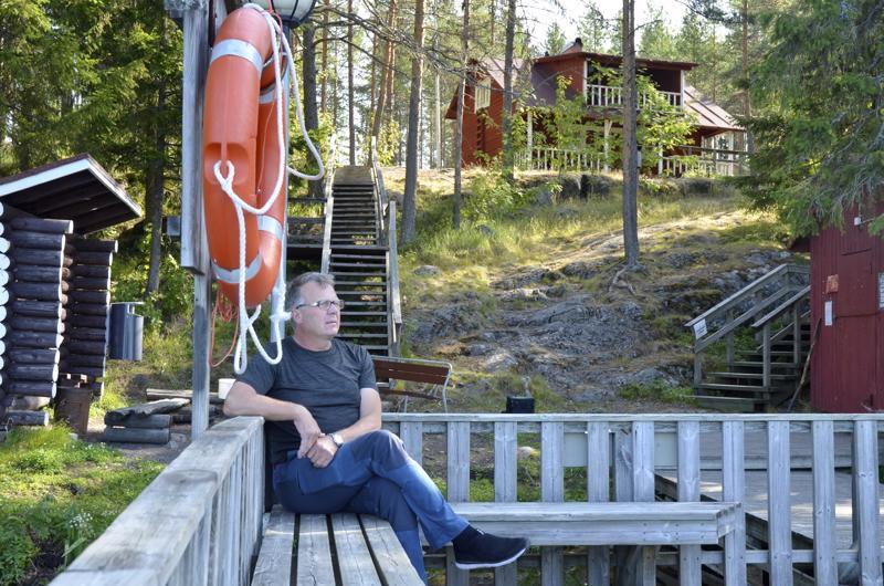 Seppo Kallio istuu rannan suosituimmalla paikalla laiturilla. Taustalla näkyy Kekan maja.