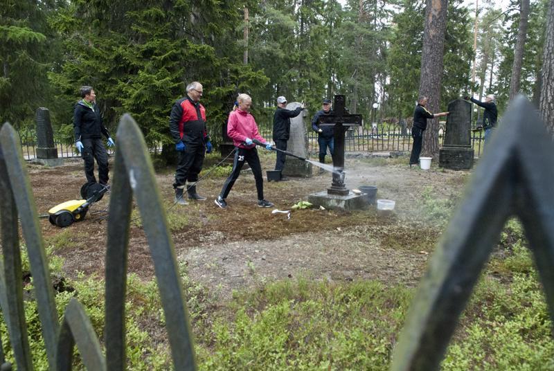 Olivia Kauppila putsaamassa Donnerien hautakiviruudussa sijaitsevaa rautaristiä. Mukana talkoissa tiistai-iltana olivat myös Tiina Kauppila, Raimo Lammi, Teuvo Lempiälä, Erkki Koittola, Harri Vainioniemi ja Eero Puumala.