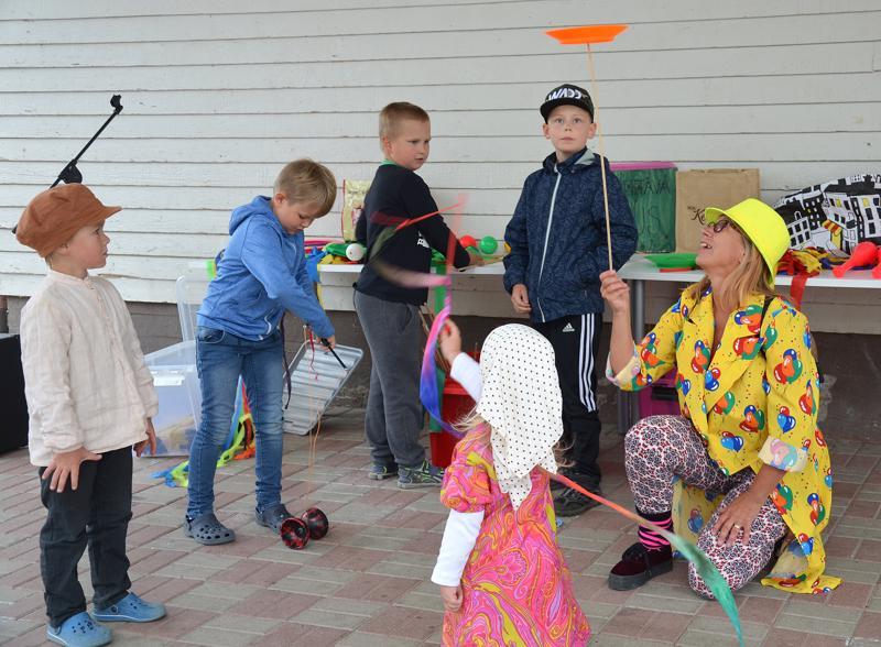 Taikuri näytti lapsille, kuinka lautasta pyöritetään kepin nokassa.