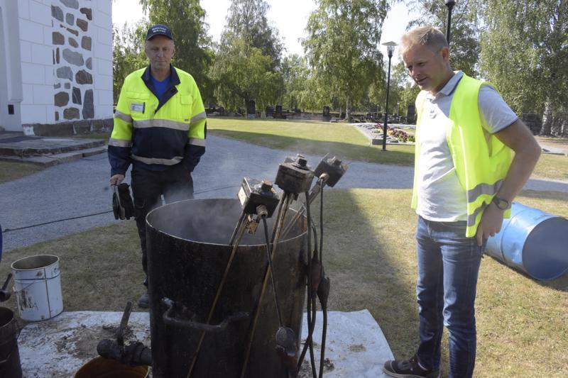 Nykarleby Spåntakin omistaja ja työjohtaja Tom Nylyd sekä seurakuntayhtymän kiinteistöpäällikkö Daniel Wikström seuraavat kuinka terva kuumennetaan ennen katolle viemistä.