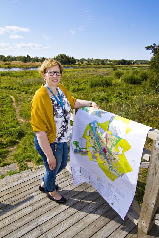 Kaavoituspäällikkö Nina Marjoniemi ja kaavaehdotuksen kartta. Toinen osayleiskaavaehdotukseen merkityistä Kalajoen ylittävistä kevyen liikenteen silloista on piirretty taustalla näkyvästä Plassin joenrantapuistosta Holmalle. Osayleiskaavaehdotuksen kartta ja paljon siihen liittyvää oheismateriaalia on nähtävänä kaupungin verkkosivuilla.
