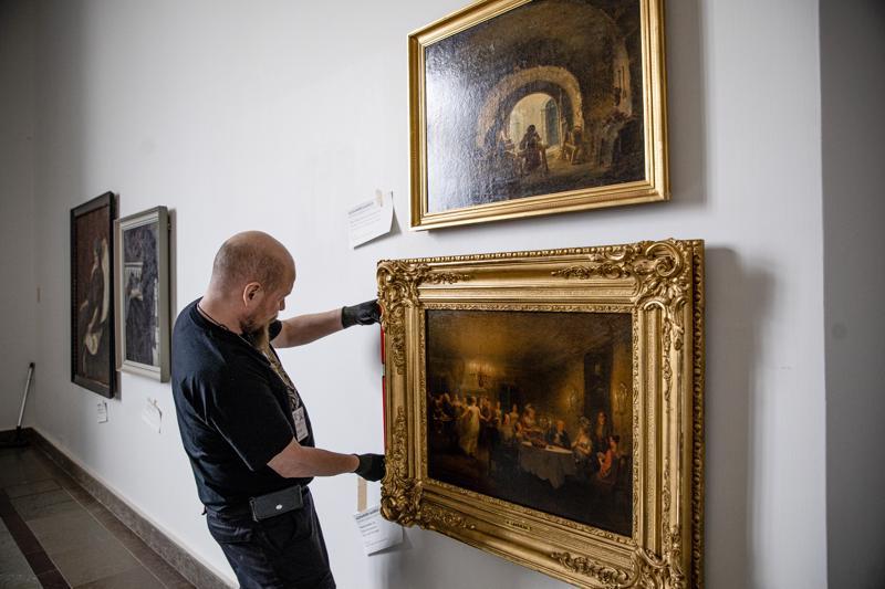 Näyttelymestari Timo Hiltunen ripusti seinälle Alexander Lauréuksen maalausta Pastorin kestit. Se on yksi Ateneumin ystävät ry:n lahjoituksista nimikkomuseolleen.