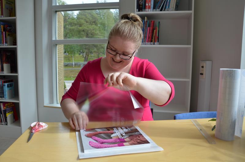 Kirjastovirkailija Noora Järvilä näyttää Kaustisen kirjastossa, kuinka kirja saadaan muoveihin ilman ikäviä ilmakuplia.