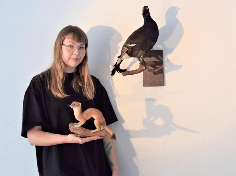 Nanna Ylönen ja täytetyt eläimet, taustalla teeri ja kädessä kärppä. Ne ovat enää varjokuvia entisestään. Performanssin avulla hän kuvailee niiden oloa elävänä ja esineenä.