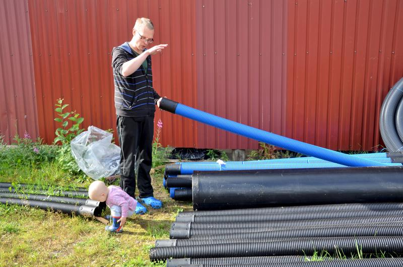 Antti Lagerbohm esittelee hänen ja vaimonsa Jenni Kentalan pihaan Halsualla tulevaa jätevesijärjestelmää. Myös Julia-tytär tarkastaa putkia.