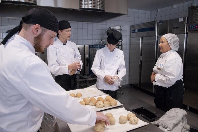 Jesse Tarkkinen, Anton Korkiakangas ja Ivan Timirov ottavat tuntumaa opetuskeittiöön. Opastamassa opettaja Saila Tolppanen.