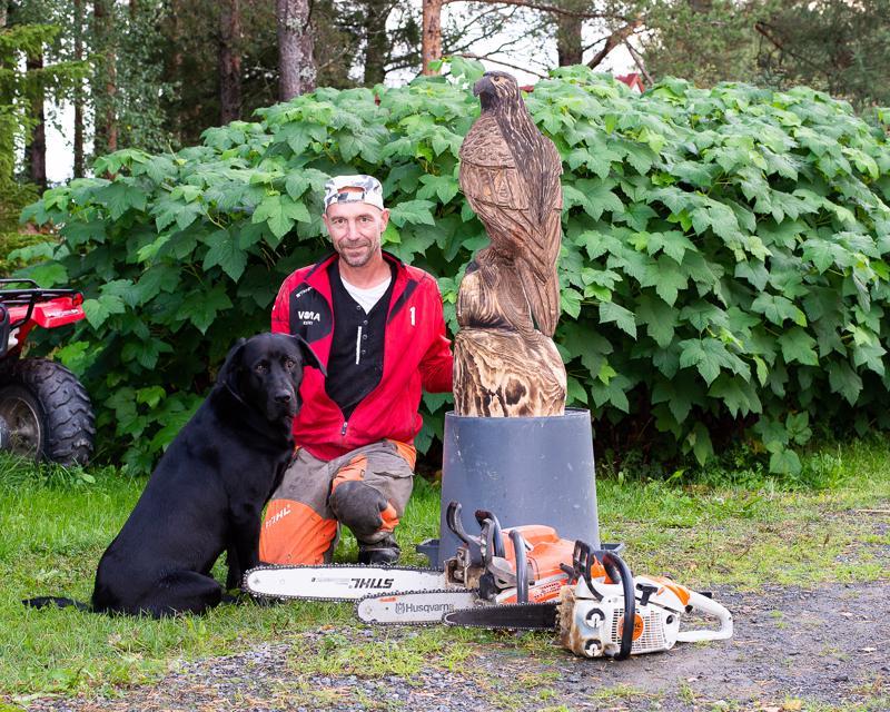 Jarkko Leppälä veistää moottorisahallaan pääasiassa kotipihassa, missä Jokke-koira pitää hänelle mieluusti seuraa.