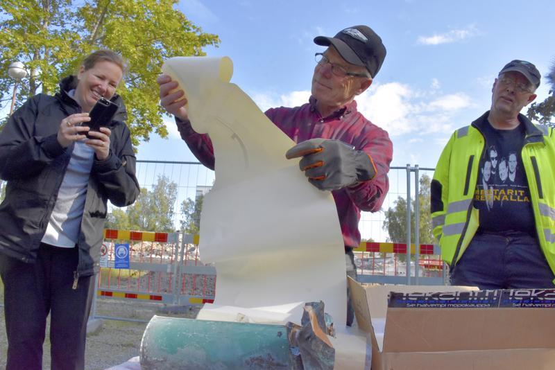 Pertti Liikanen on saksinut kuparikapselin auki. Sen uumenista löytyy muun muassa Pursisalmen koulun piirustukset. Koulun entisiä oppilaita on myös Osmo Samanen. Koulun purkutöistä vastaava kiinteistöyhtiö Ebban toimitusjohtaja Åsa Björkman ikuistaa tilannetta.