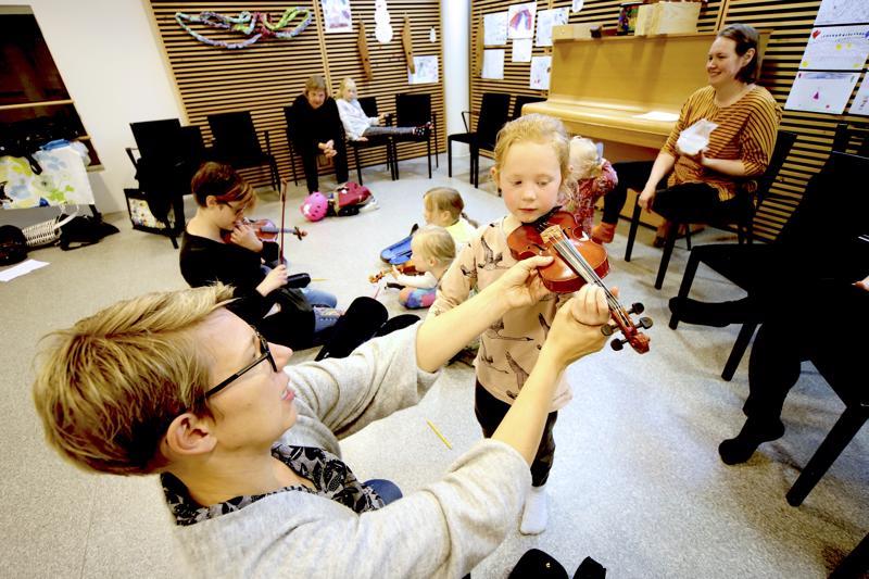 Siiri Järvelä sovittaa Eliida Timoselle viulua Näppäreiden järjestämällä ensimmäisellä alkeisryhmätunnilla. Eliida on haaveillut viulunsoitosta jo parin vuoden ajan ja nyt eskari-iässä soittotunnit tulivat ajankohtaisiksi.