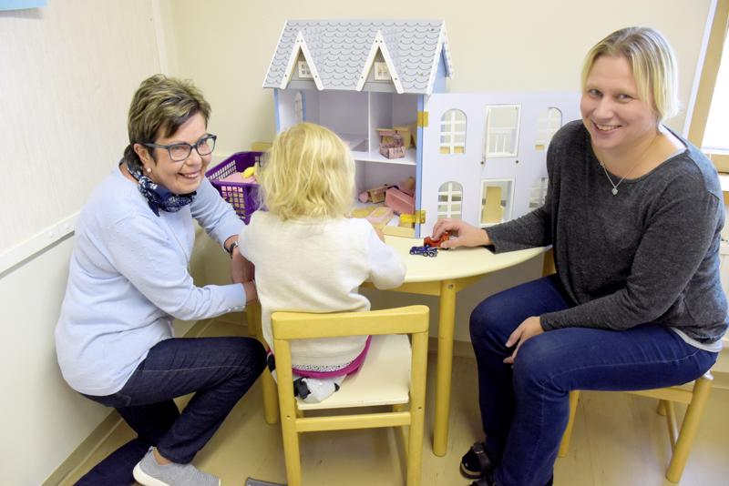 Päiväkodin johtaja Carola Koivu (vas.) ja varhaiskasvatusopettaja Linda Tast kalustavat nukkekotia yhdessä Tindran (4) kanssa.
