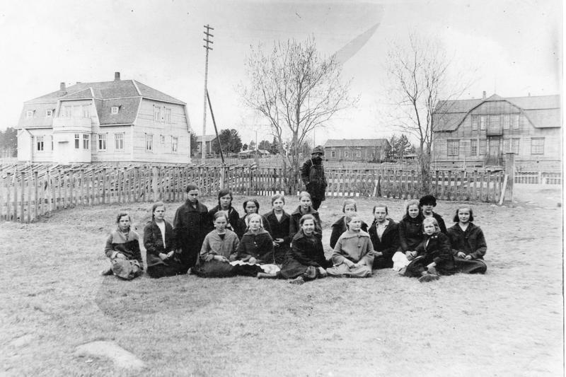 Yhteiskoulun tyttöjä vuonna 1926. Taustalla oikealla jo maisemasta hävinnyt vanha koulurakennus, vasemmalla Myyrilä lähes nykyisessä asussaan.
