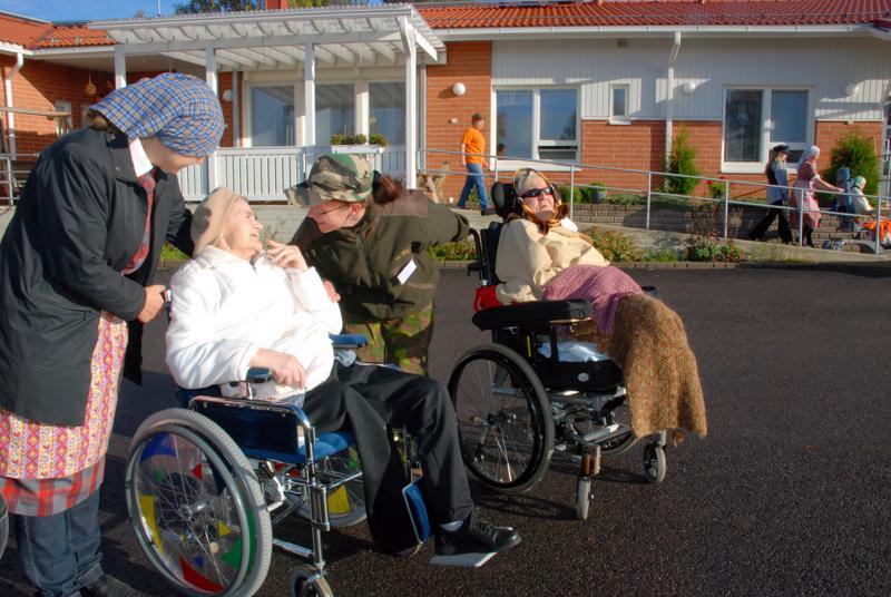 Pohjois-Suomen koulutuskeskuksen lähihoitaja-opiskelijat olivat järjestäneet Kartanonväessä toimintapäivän vanhustenviikon tiimoilta. Kuvassa Riina Mattila ja Eira Kemppainen onnittelevat Aunea, jolla oli 80-vuotispäivä.