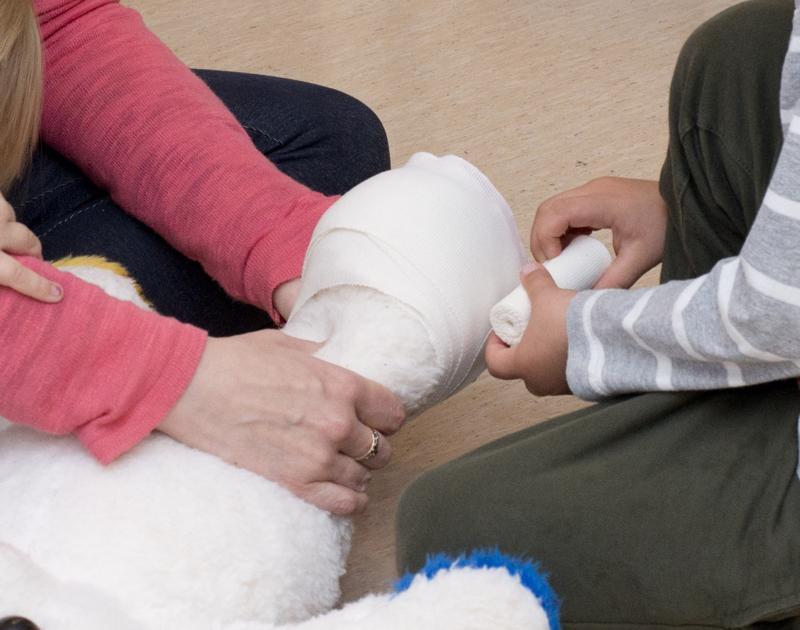 Lapset opettelivat ensi-aputaitoja yhdessä MLL:n perhekerhossa. Nalle oli nyrjäyttänyt nilkkansa ja se piti sitoa asianmukaisesti.
