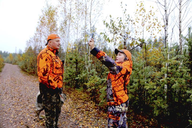 Aaro Peltoniemi etsii kännykkään kenttää, jotta karttasovellus kertoisi missä muut metsästäjät ovat. Toni-isä ja norjanhirvikoira Jate seuraavat vieressä.