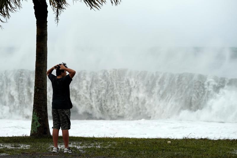 Poika ihmetteli lauantaina taifuunin nostattamia aaltoja Japanin Atawassa.