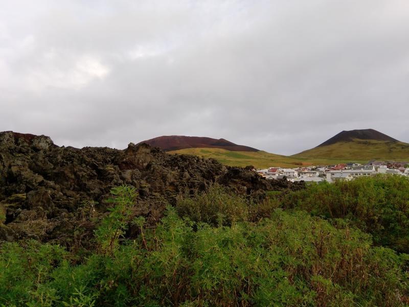 Kaupunkia ympäröivää laavakivikko on syntynyt vuoden 1973 purkauksessa. Horisontissa näkyvät tulivuoret Eldfell ja Helgafell.