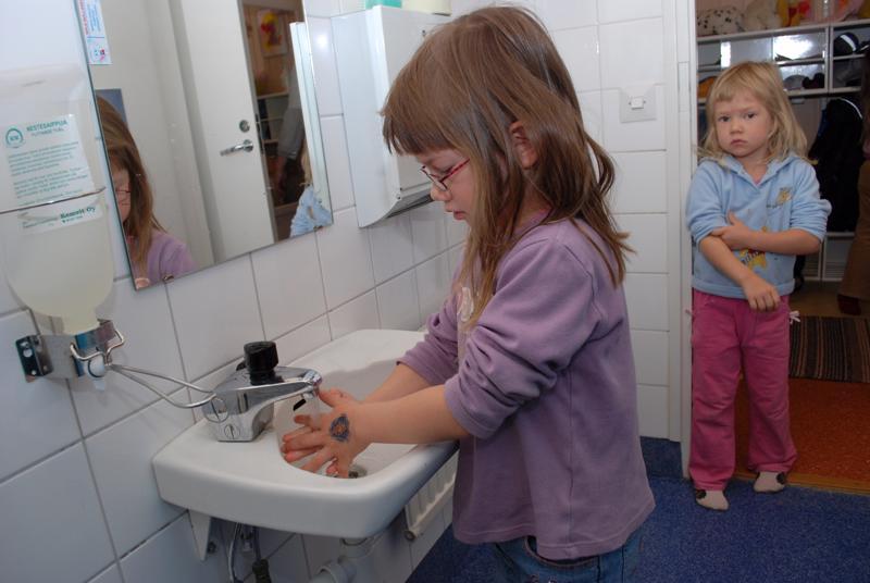 Päiväkodeissa pestiin urakalla käsiä sikainfluessaepidemian välttämiseksi. Ahjolassa käsien pesulla Mira Laukka ja vuoroa odottamassa Meri-Tuulia Laukka
