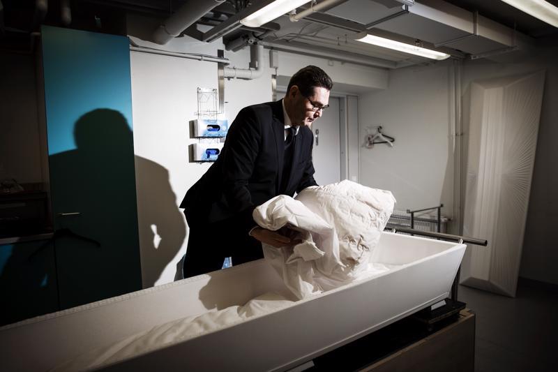 """Petri Lajunen kutsuu itseään hauturiksi eikä pidä hautausurakoitsija-nimikeestä. """"Ei hautaaminen ole mitään urakointia"""", hän muistuttaa. Tässä hän valmistelee arkkua vainajaa varten sairaalan ruumishuoneella."""