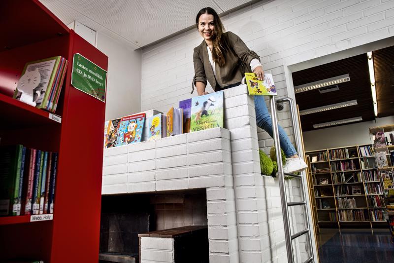 Hannele Lampela esittelee lapsuutensa lukunurkkaa Ylivieskan kirjastossa.