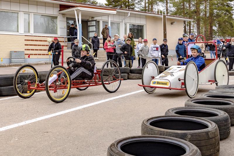 Kuvassa mäkiautokisailijoita Mäkirinteen koulun pihalla.